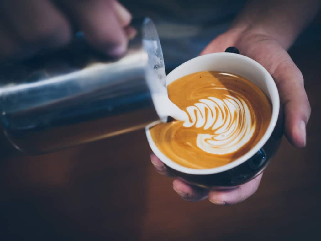 Close up of person pouring milk into coffee cup