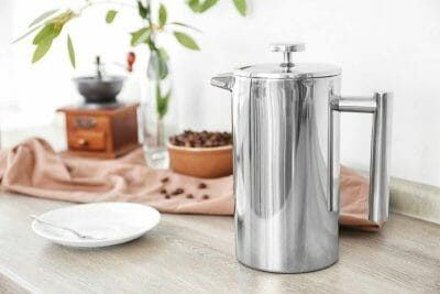Stainless steel coffee press on table