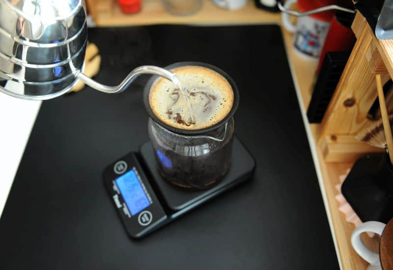 Digital coffee scale on bench with gooseneck kettle pouring over ground beans