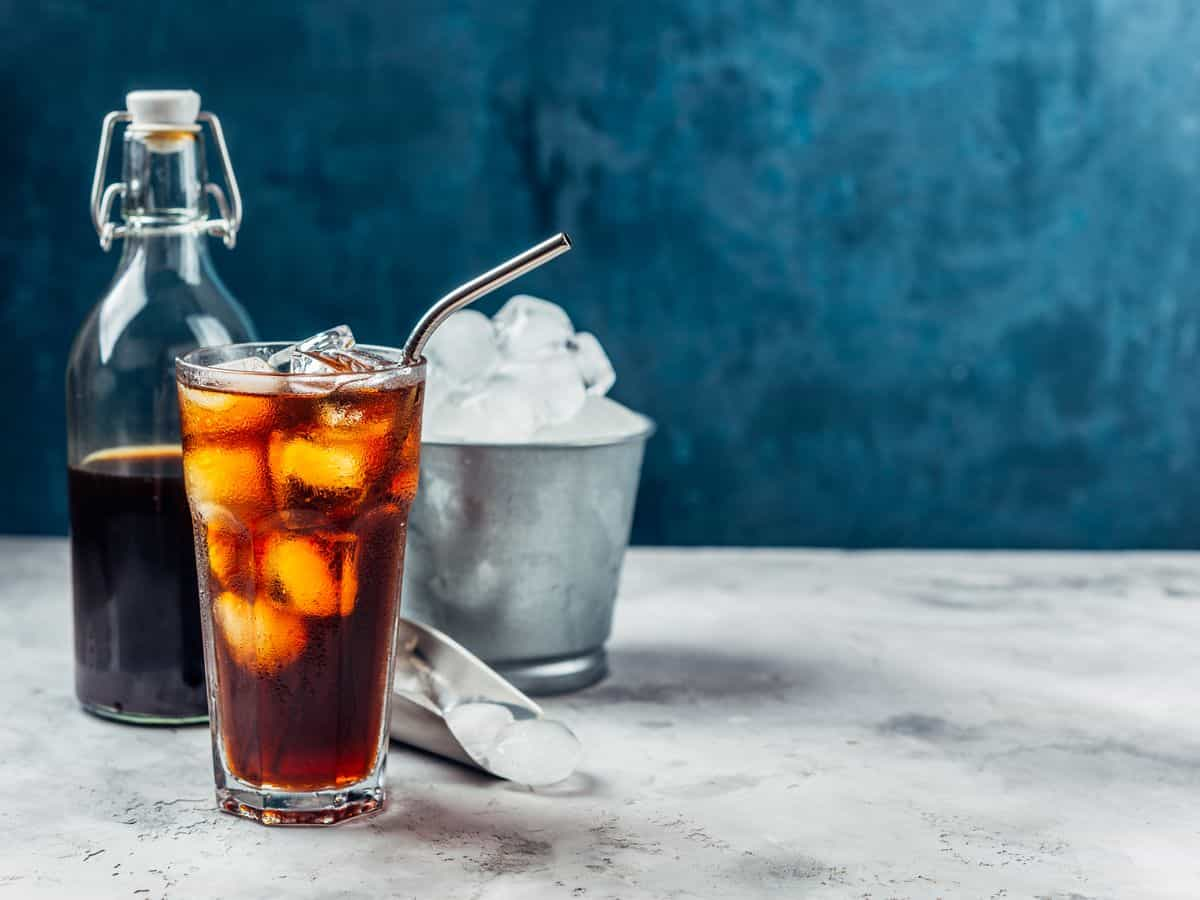 Black cold brew coffee in a glass with metal straw