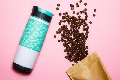 Stainless steel travel coffee tumbler on pink background