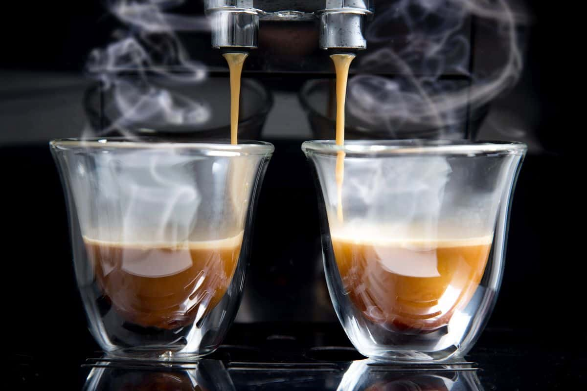 two glass mugs with espresso on automatic coffee machine drip tray