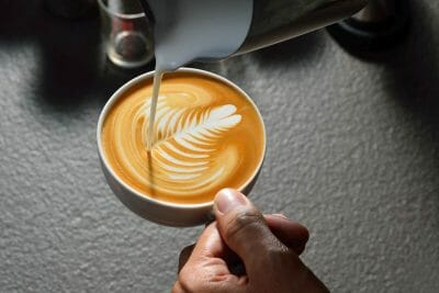 best milk frother pouring milk into cup to make latte art