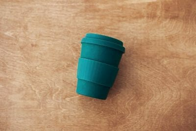 Stylish reusable eco coffee cup on wooden background, flat lay