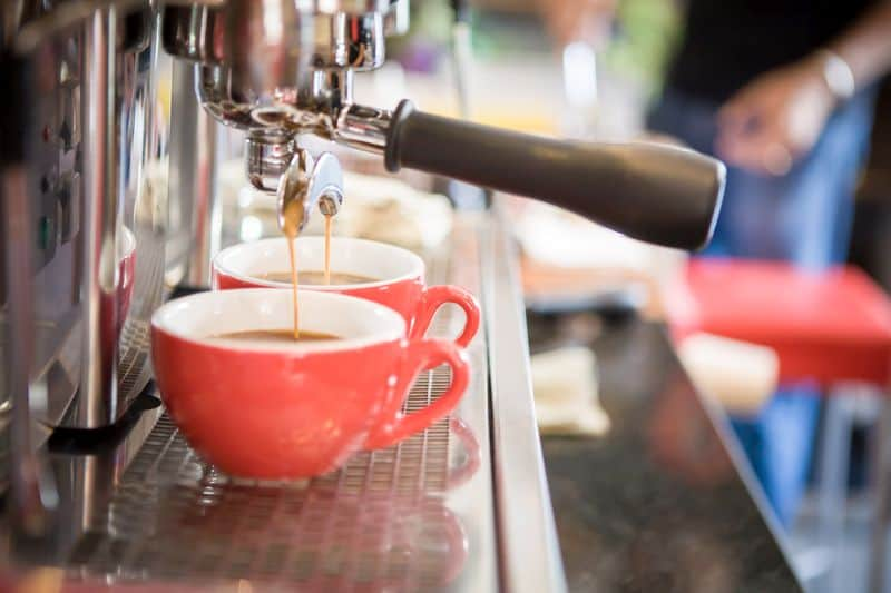 extracting espresso shot into red coffee cups