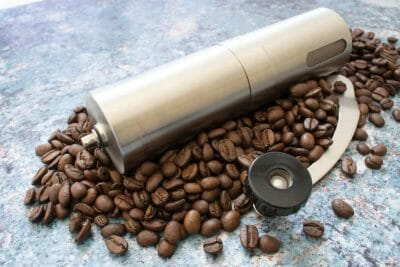 Stainless steel manual coffee grinder sitting on top of roasted coffee beans