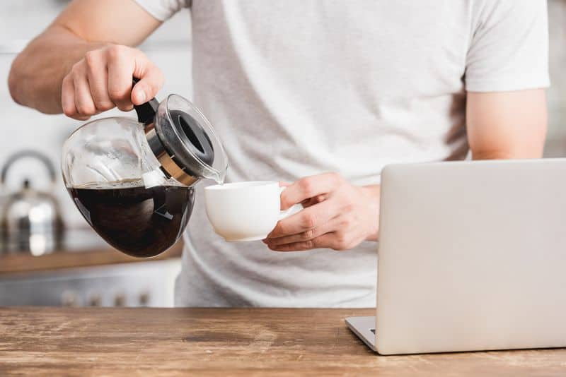 Man pouring coffee from drip coffee pot into cup