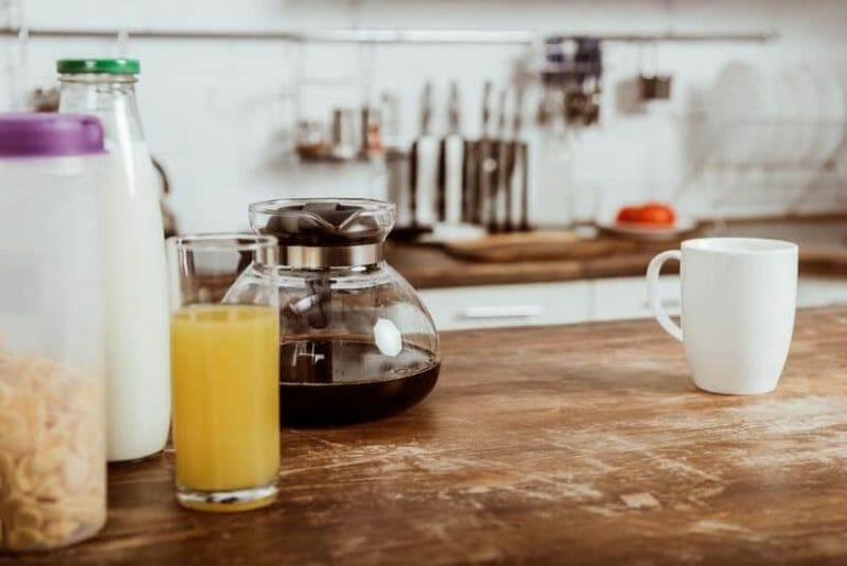 Kitchen bench with glass coffee carafe and coffee mug.