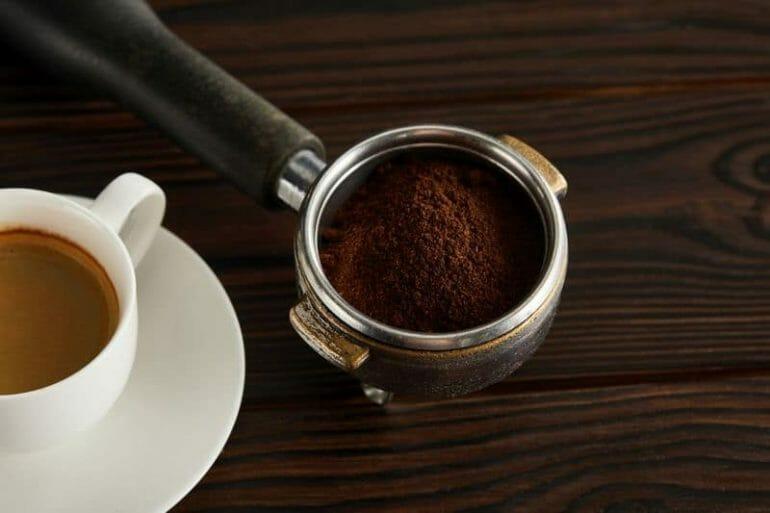 cup of espresso with espresso machine portafilter and ground coffee