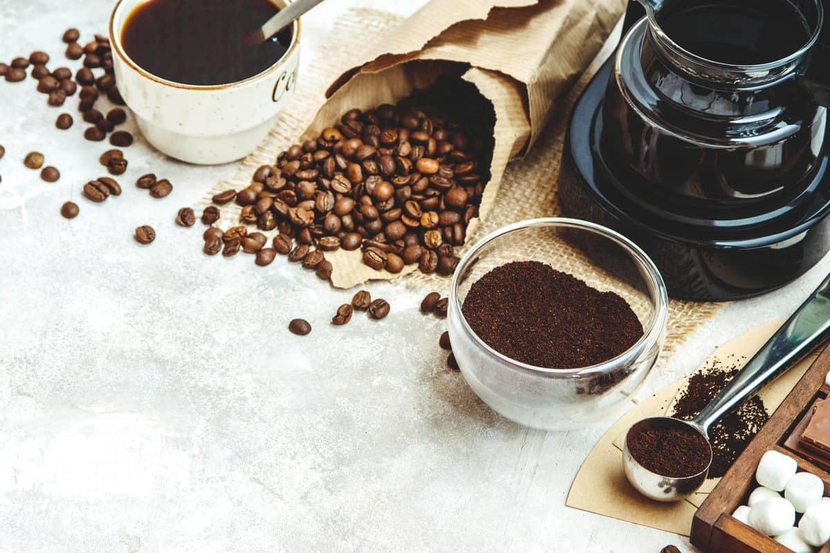 Coffee pot with ground coffee, coffee beans and mug
