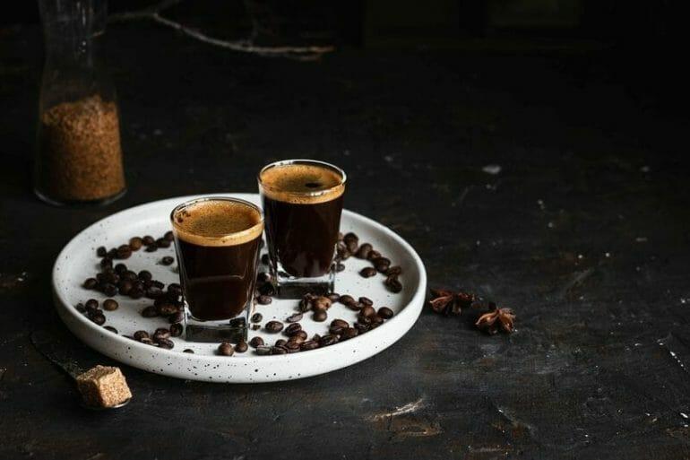 two glasses of espresso on white tray