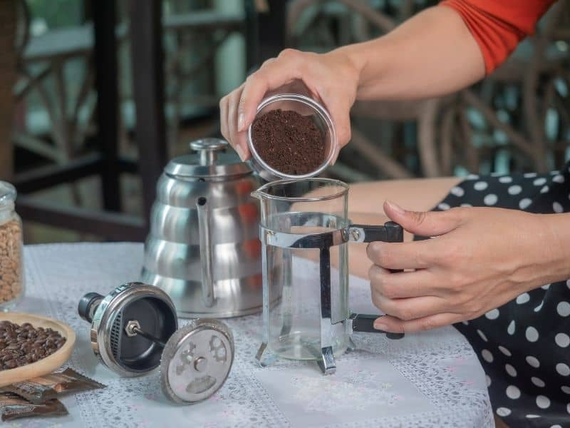 Woman pouring ground coffee into empty coffee press.