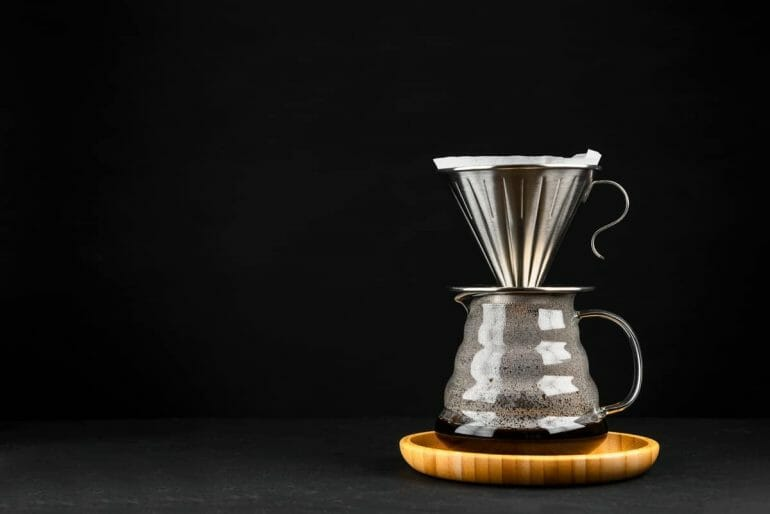 Stainless steel pour over dripper over glass server with freshly brewed coffee.