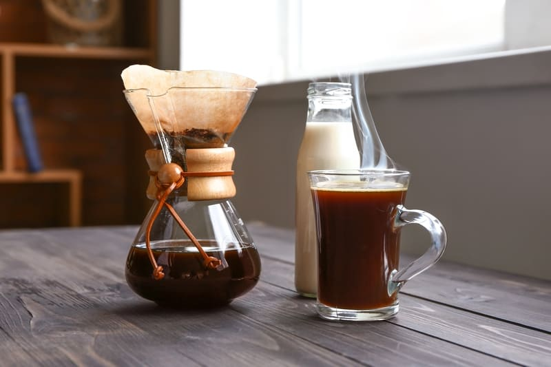 Brewed coffee in chemex and glass with bottle of milk on wooden table