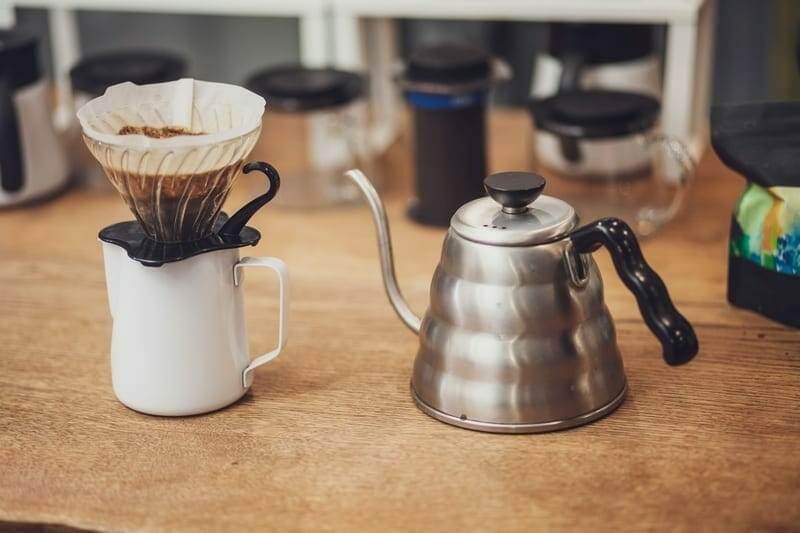 Alternative coffee. Single cup dripper with filter and coffee over the cup and metal kettle.