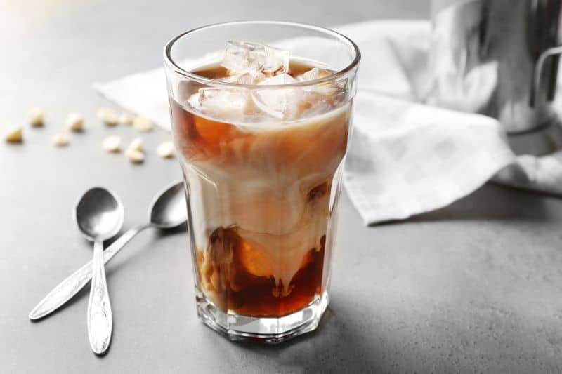Glass of iced cold brewed coffee with spoons on table.