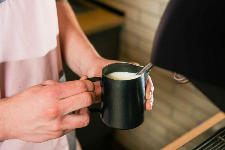 Hands holding cup with milk for coffee with machine. Barista with espresso milk pitcher make milk foam.