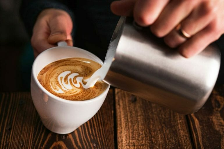 Barista pouring milk into cappuccino cup with espresso milk pitcher and making latte art.