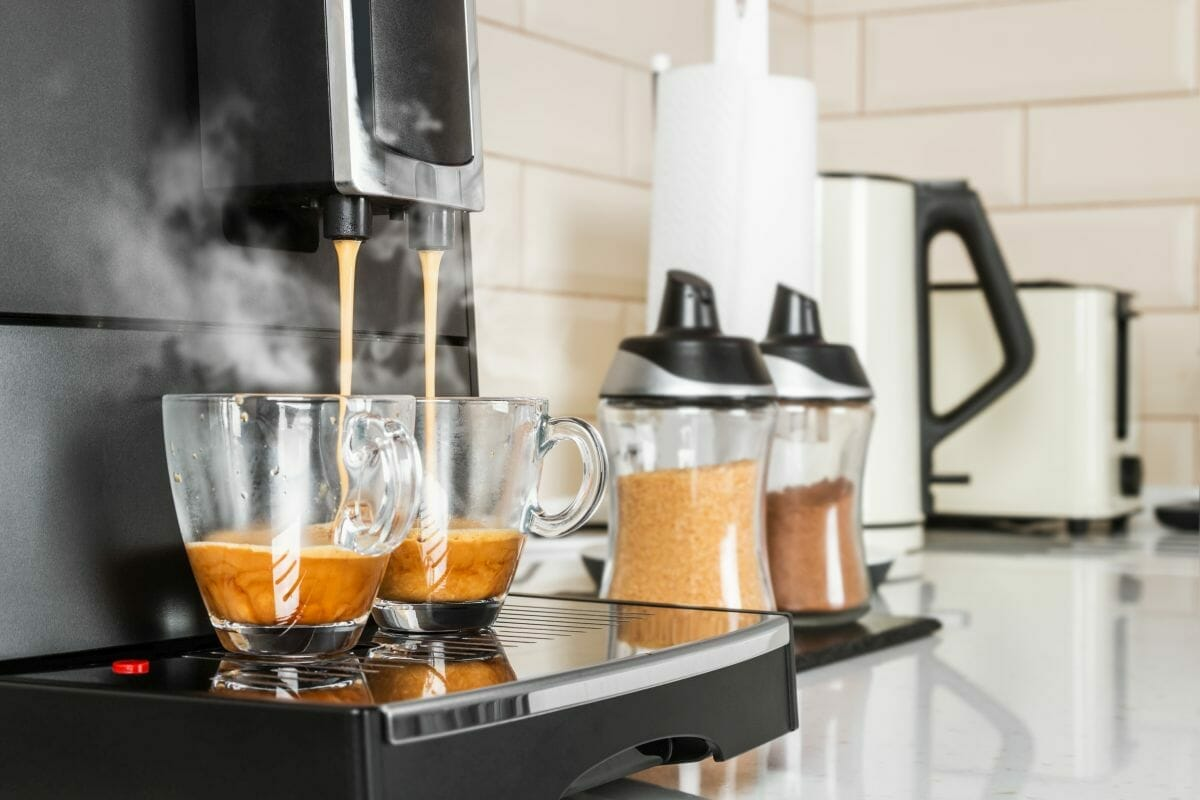 hot coffee from the home coffee machine is poured into glass cups