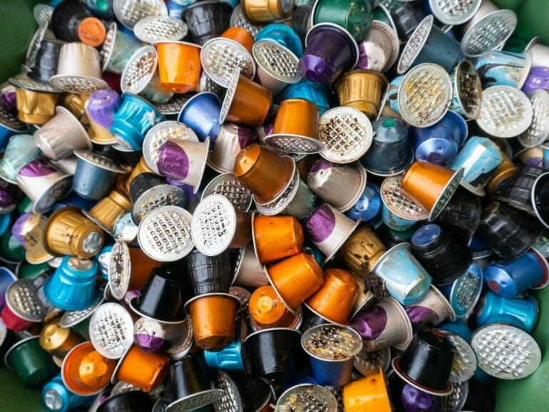 Used coffee capsules rubbish in many different colours in a disposal waste container.