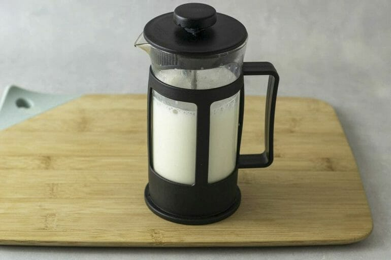 Using a french press to froth milk.