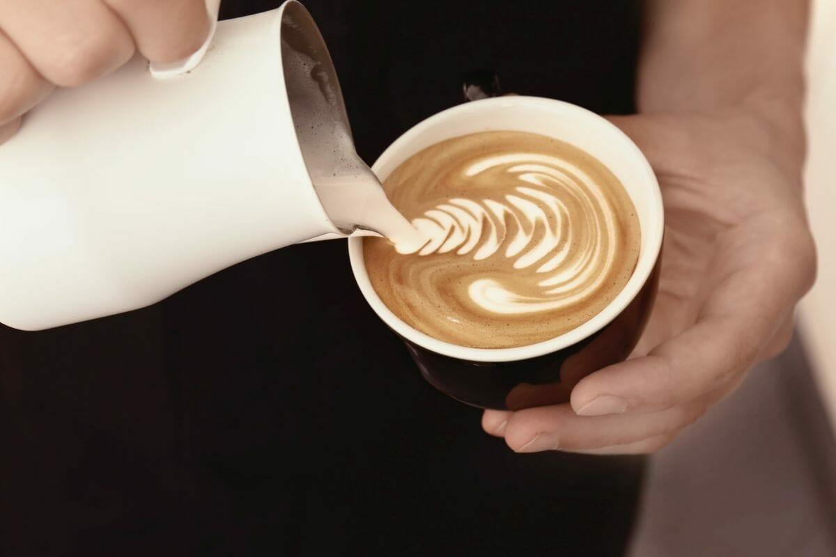 pouring frothed milk into coffee cup with milk pitcher.