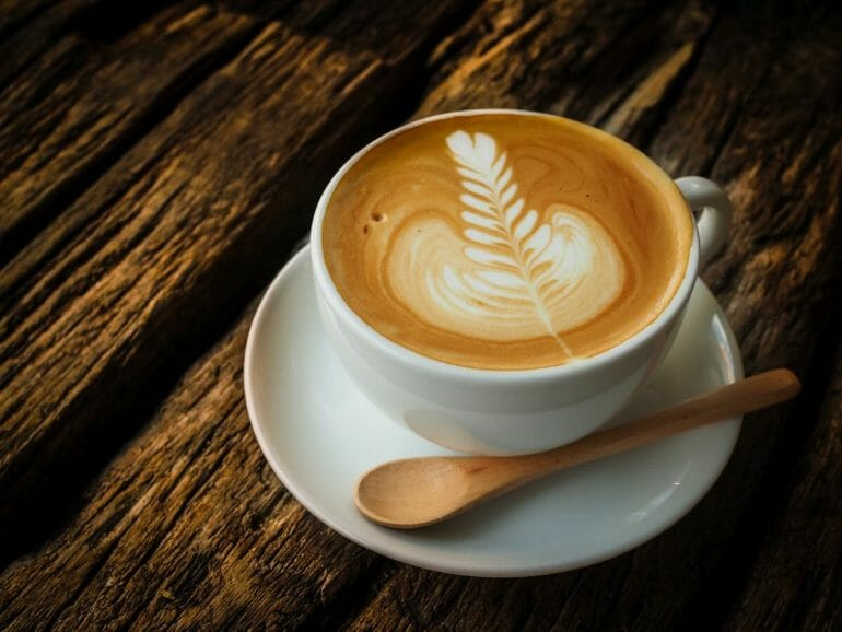 white coffee cup with latte art on wooden bench top.