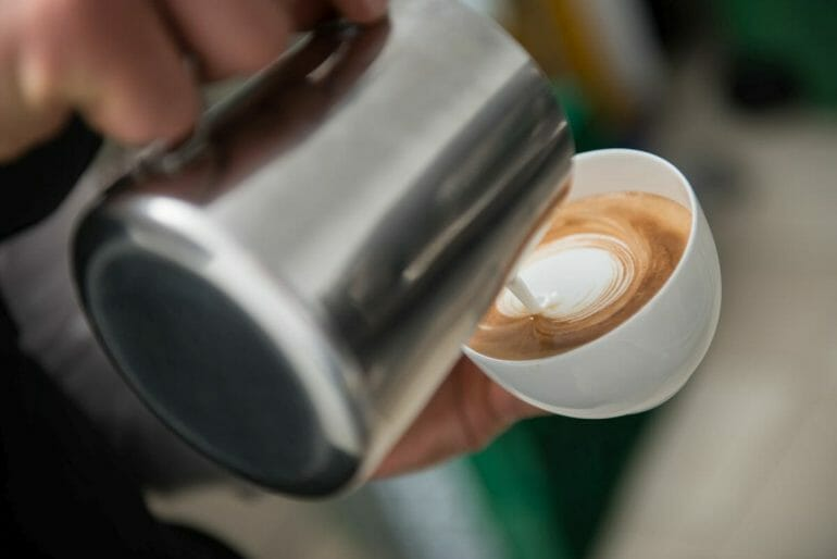 Barista pouring milk into the cup of coffee making latte art.