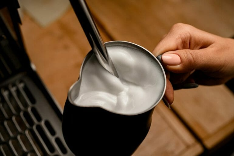 high angle view of fresh steamed milk foam in jug in woman's hand.