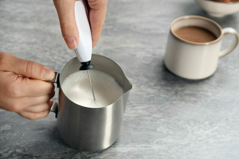 Woman using handheld milk frother in pitcher near cup of coffee on table.