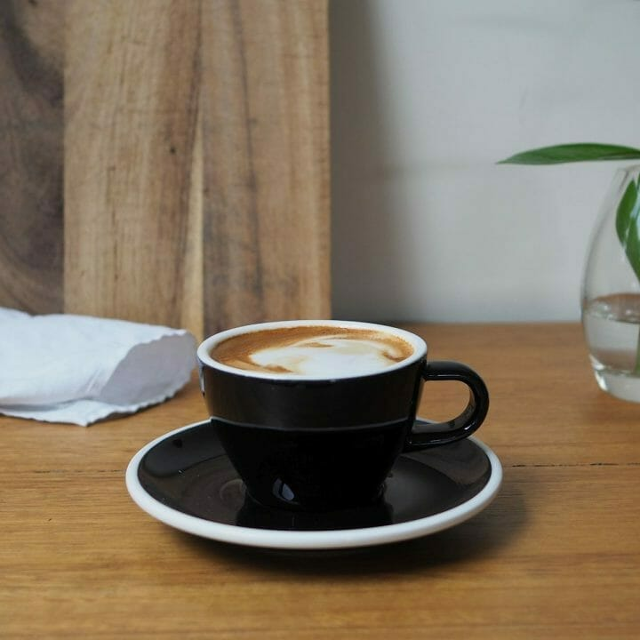 magic coffee in black cup and saucer on wooden bench top.