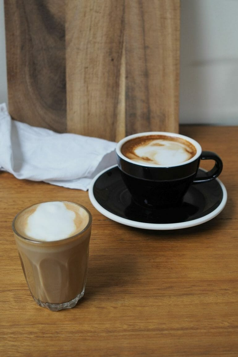 piccolo latte and magic coffee drinks on wooden benchtop.