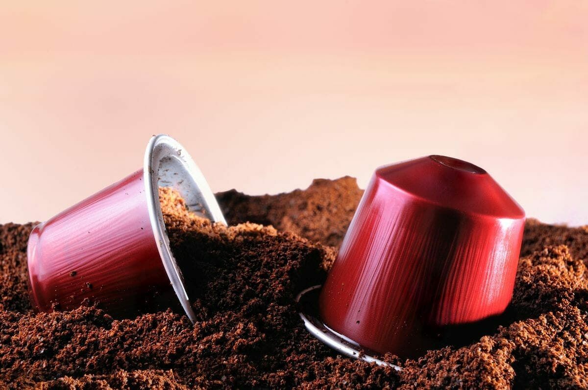 refillable capsules for espresso coffee machine on heap of ground coffee.